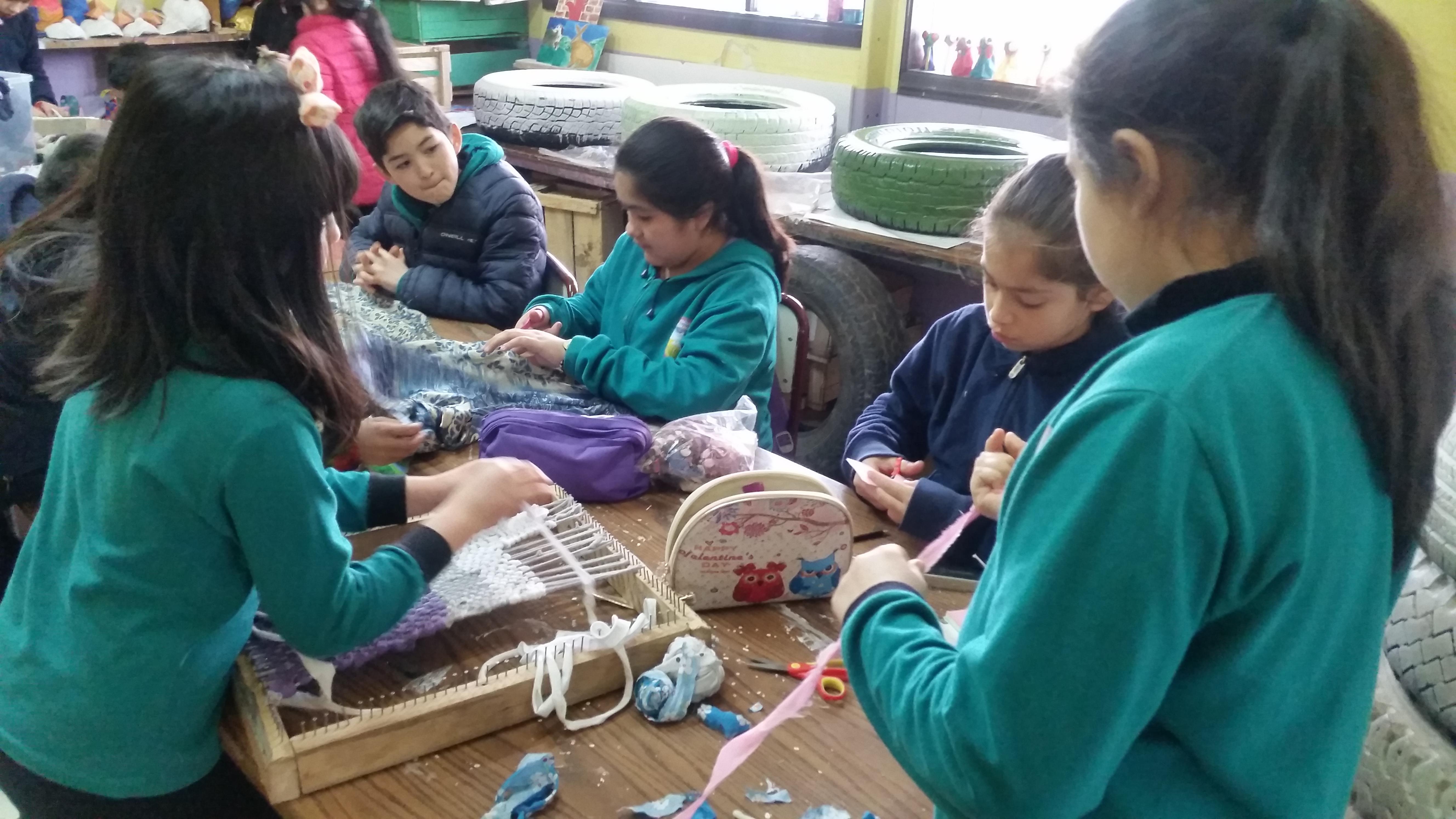 niños cortando genero para elaborar telar